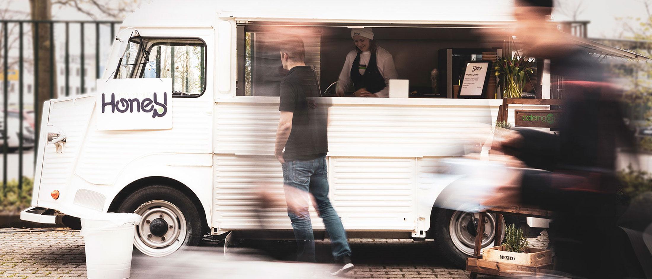 Food-Truck HoneY von cateringart. Im Truck steht eine junge Frau mit einer Schürze, vor dem Truck ein Kunde.